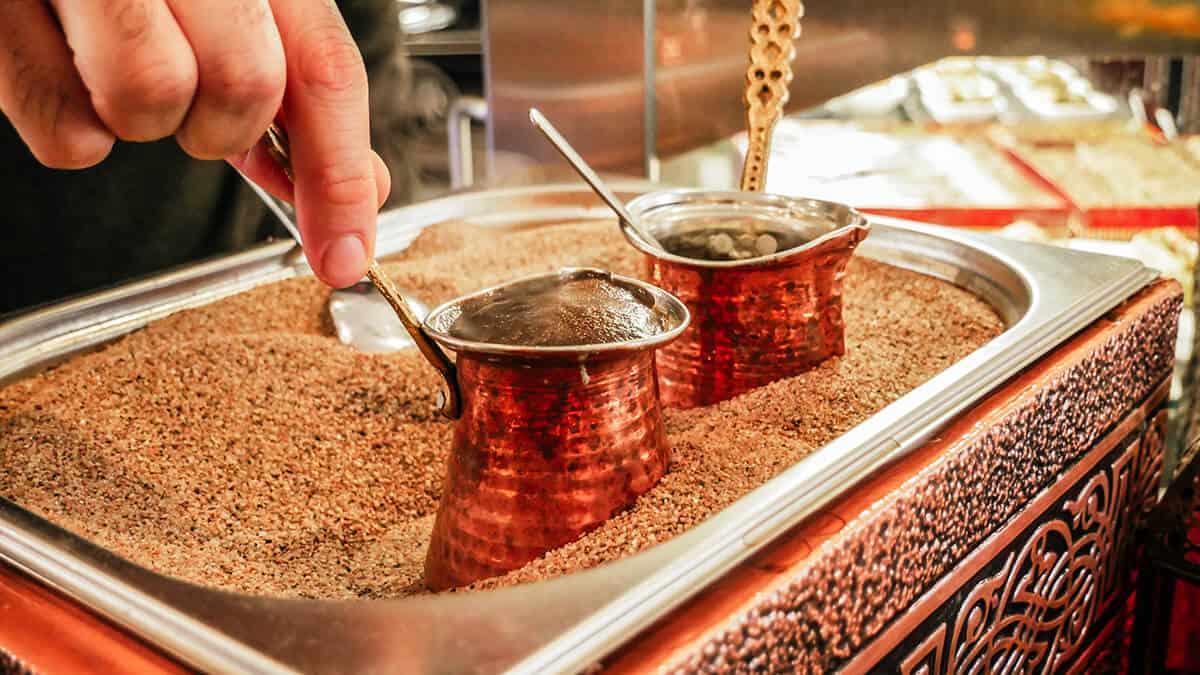 Kaffeekannen im heißen Sand