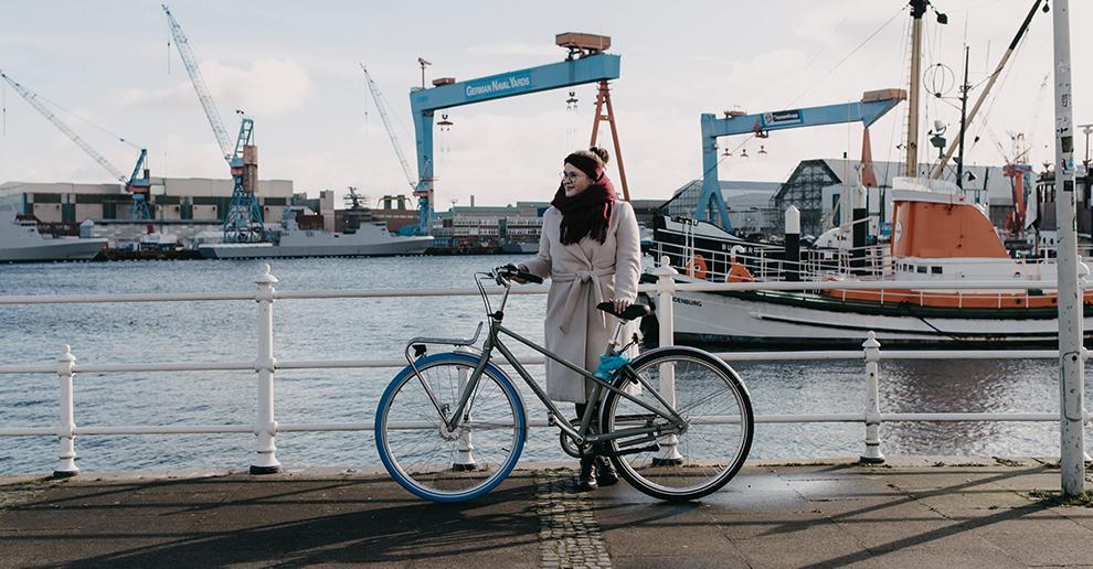 Mädchen mit beigem Mantel und Swapfiets-Fahrrad steht am Wasser