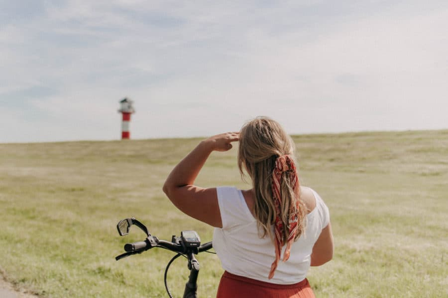 Mädchen auf Fahrrad vor Leuchtturm in Glückstadt